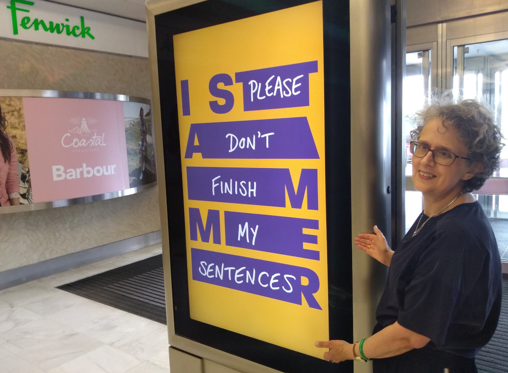 "Christine with a Stamma poster saying ""I stammer"" and ""Please don't finish my sentences""."