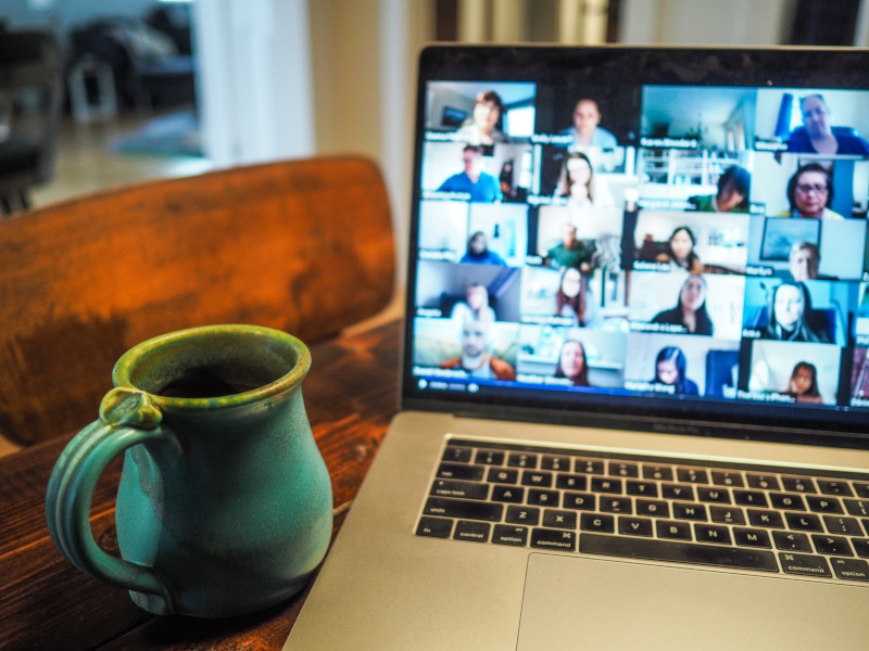 Computer at home next to a mug, with computer screen showing participants in a video conference.